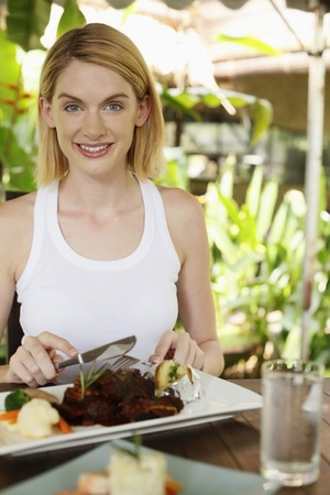 Woman with a plate of lamb shank Stock Photo - 8606145
