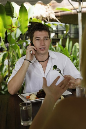Man and woman eating at a cafe, man talking on the phone Stock Photo - 8606113