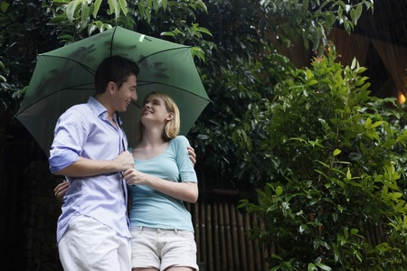 Man and woman sharing an umbrella photo