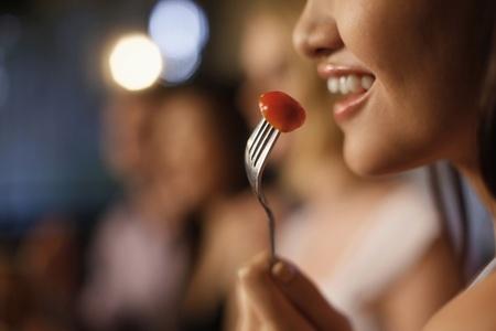 tomate cerise: Femme de manger des tomates cerises, gros plan