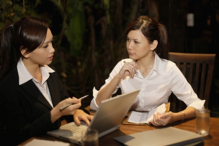 Businesswomen having discussion at a cafe photo