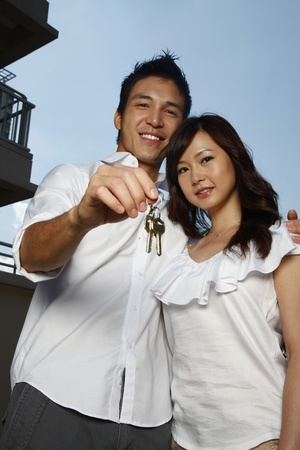 Man and woman with key to their new home photo