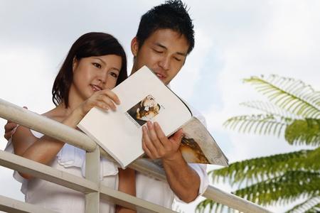 Man and woman reading magazine photo