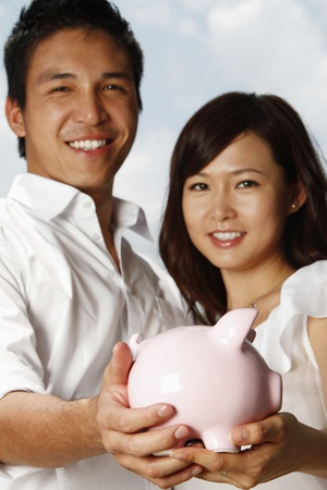 Man and woman holding piggy bank photo
