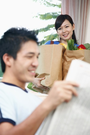 Man reading newspaper, woman carrying groceries in the background photo
