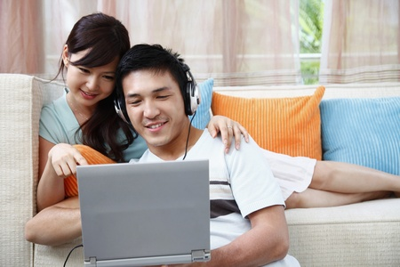 Man and woman using laptop, man with headphones Stock Photo - 8606093