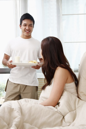 Man bringing breakfast to woman photo