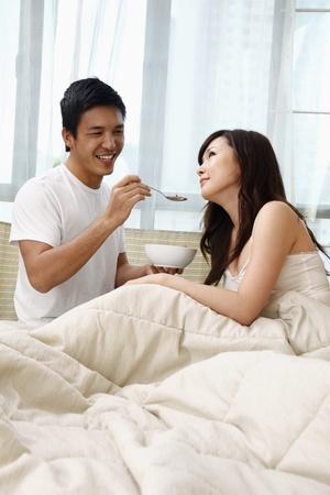 Man feeding woman cereal photo