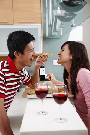 Man feeding woman pizza photo