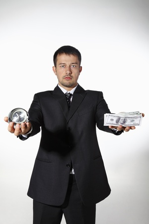 Businessman holding clock and money photo