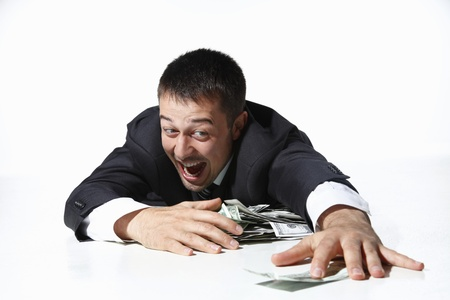 Businessman gathering all the money on floor photo
