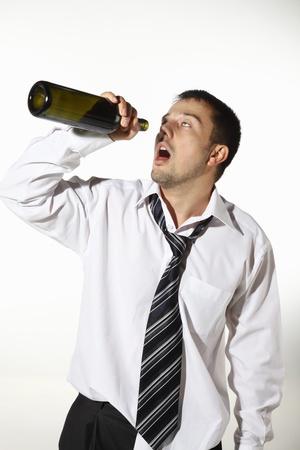 Drunk businessman drinking from an empty bottle