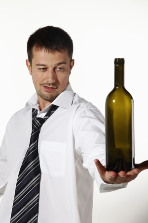 Drunk businessman balancing bottle on his palm photo