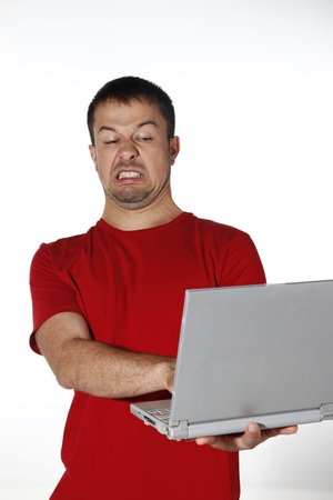 Man looking disgusted while using laptop Stock Photo - 8605930