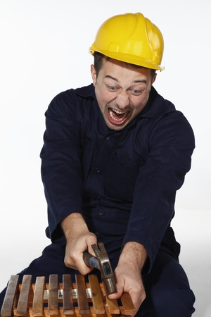 accident de travail: Homme frapper son pouce avec un marteau.