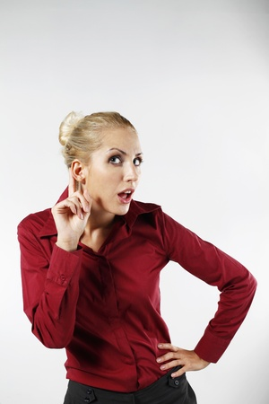 belarusian ethnicity: Businesswoman with finger to ear trying to listen Stock Photo