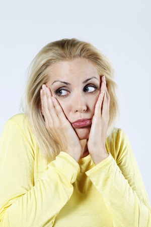 Woman with hands on cheeks while looking away photo