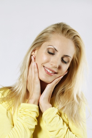 belarusian ethnicity: Woman smiling while touching her face