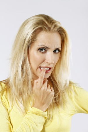 Woman biting her finger while thinking photo