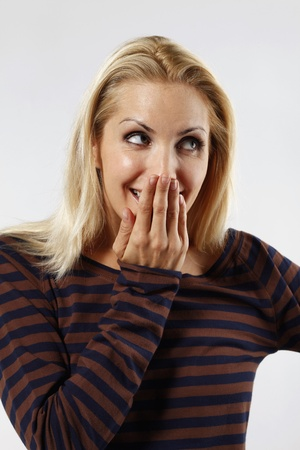 Woman covering her mouth with hand while giggling photo