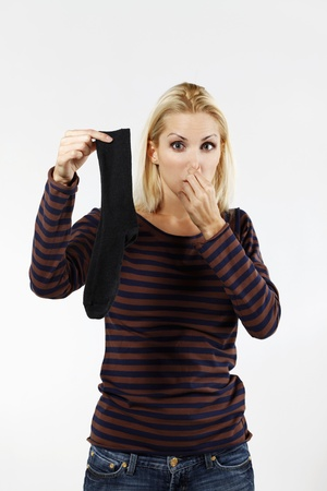pinching: Woman pinching nose while holding socks Stock Photo