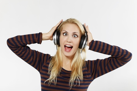Woman crossing eyes while listening to music on the headphones photo