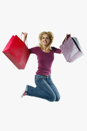 Woman holding shopping bags while jumping on a trampoline Stock Photo - 8735656