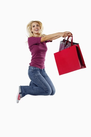 Woman holding shopping bags while jumping on a trampoline Stock Photo - 8735671