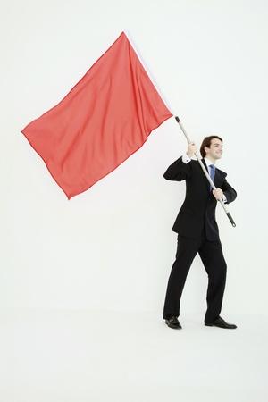 red man: Empresario permanente con bandera roja en sus manos