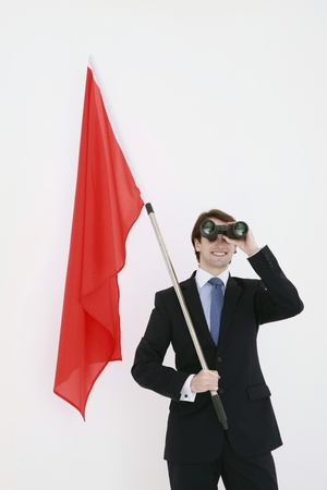 Businessman with red flag in his hand looking through binoculars Stock Photo - 8758409
