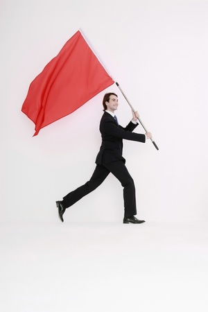 Businessman walking and waving a red flag in his hands photo