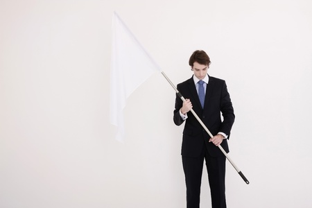 Businessman holding a while flag Stock Photo - 8757990