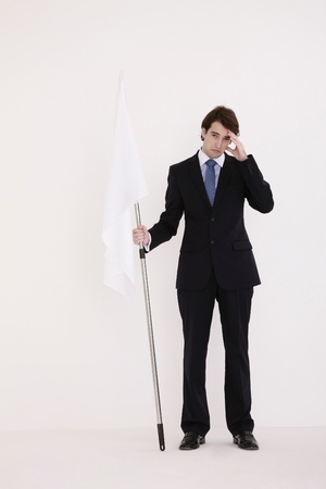 Businessman holding a while flag with head in hands Stock Photo - 8758026