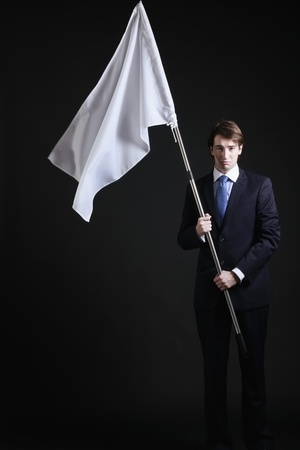 Businessman holding a while flag with a sad face Stock Photo - 8758321