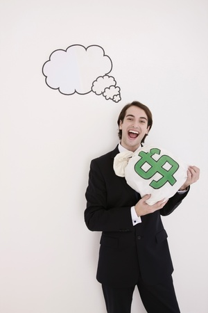 Businessman holding money bag with thought bubble above his head photo