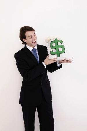 Businessman smiling at money bag Stock Photo - 8758023