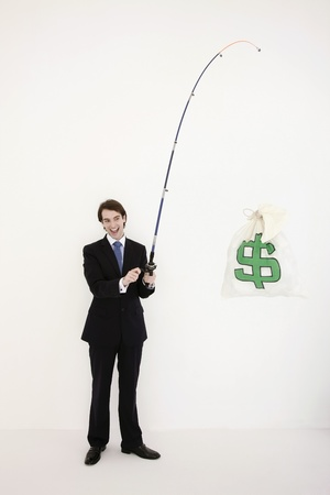 Businessman fishing out a money bag photo