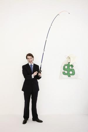 man fishing: Businessman fishing out a money bag