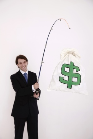 corporate greed: Businessman fishing out a money bag