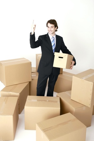 Businessman standing among cardboard boxes gesturing with finger photo
