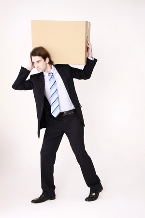 Businessman lifting a cardboard box on his shoulder photo