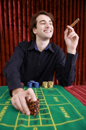 Man placing bets on gaming table photo