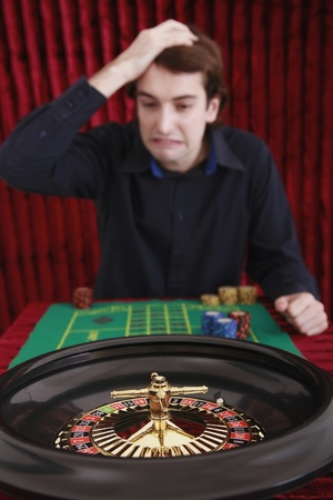 Man with hand on head at roulette table gambling photo