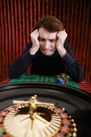 Man losing in roulette at casino photo