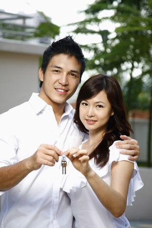 Man and woman with key to their new home Stock Photo - 8771794