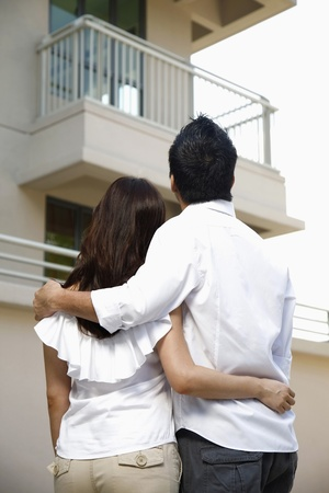a lifestyle: Man and woman embracing, looking at their new home