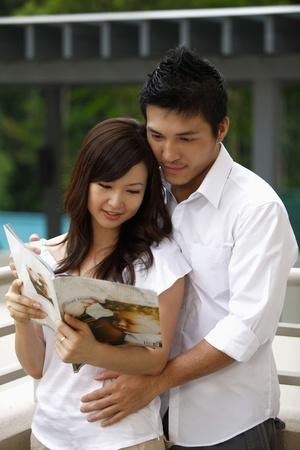 Man and woman reading magazine photo