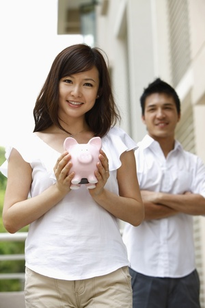 Woman holding piggy bank, man standing in the background photo