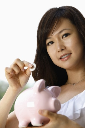 Woman putting coin into piggy bank photo
