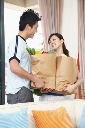 Man helping woman to carry groceries photo